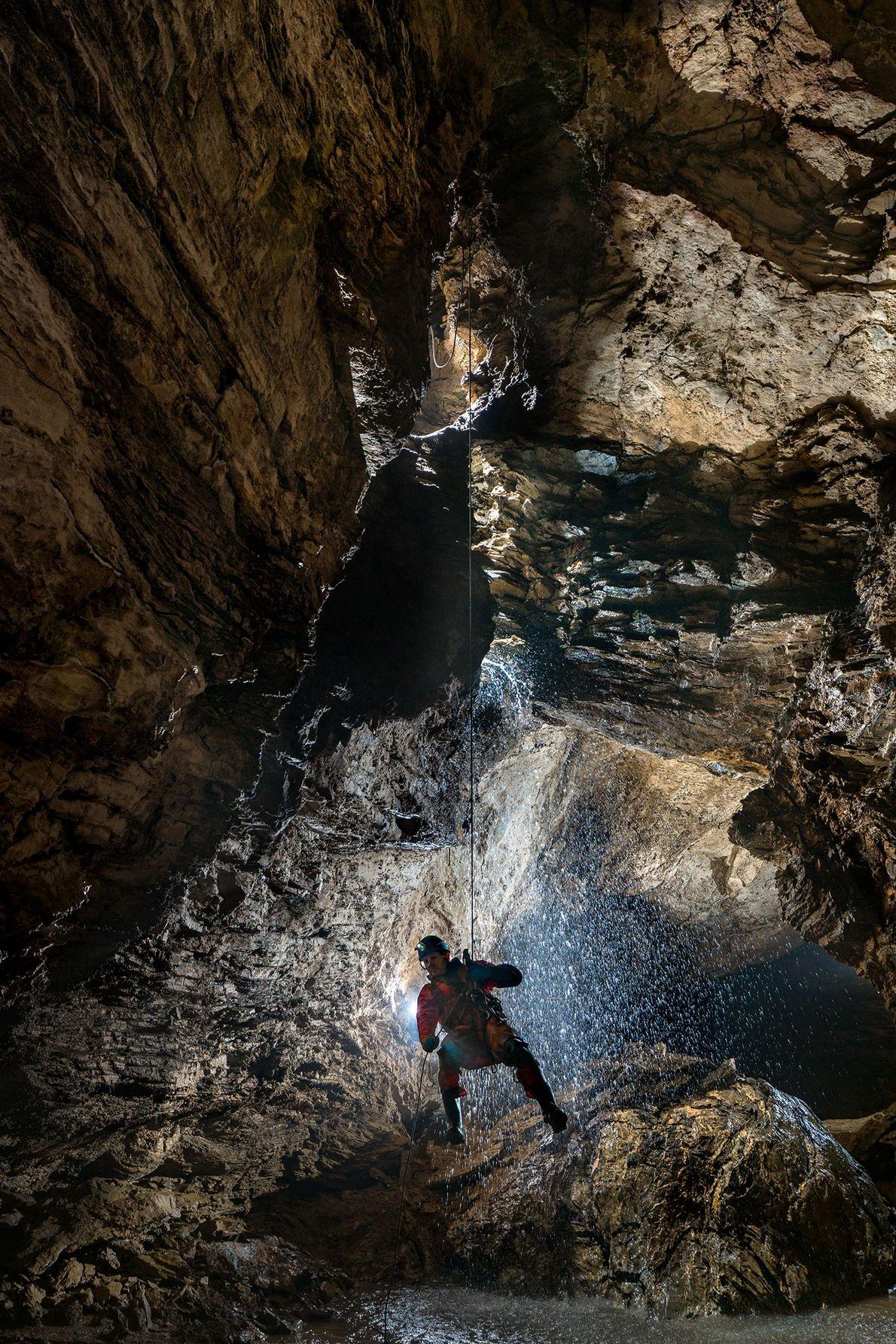 El espeleólogo inglés, Martin Hoof, uno de los numerosos miembros internacionales del equipo de expedición, desciende ...