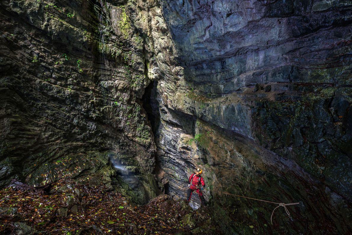 David Tirado Hernandez examina un hilo de agua que cae de la pared a medida que ...
