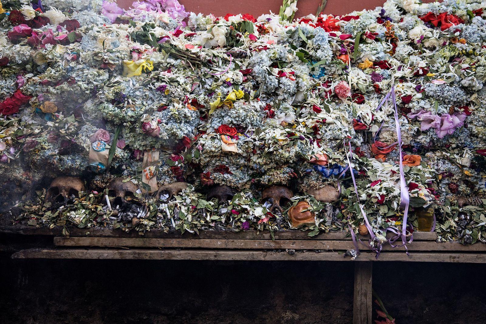 Los sepultureros regresan los cráneos y sus mantas de flores en la sepultura comunal hasta el ...