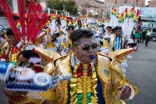 Una procesión de bailarines que usan un vestuario con plumas y lentejuelas salen a las calles ...