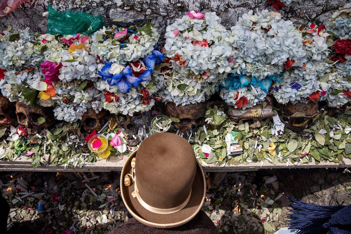Una mujer Aymara está de pie sobre la fosa común llevando un vestido tradicional. Según la ...