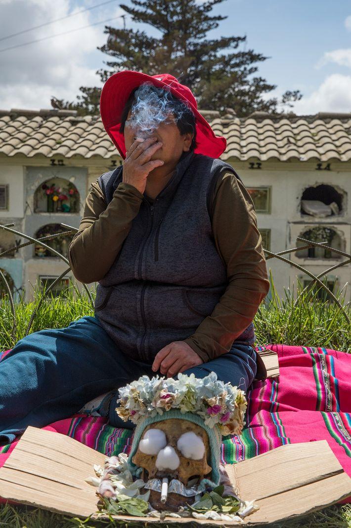 Los participantes esparcen mantas de picnic en el cementerio para disfrutar en compañía de los difuntos ...