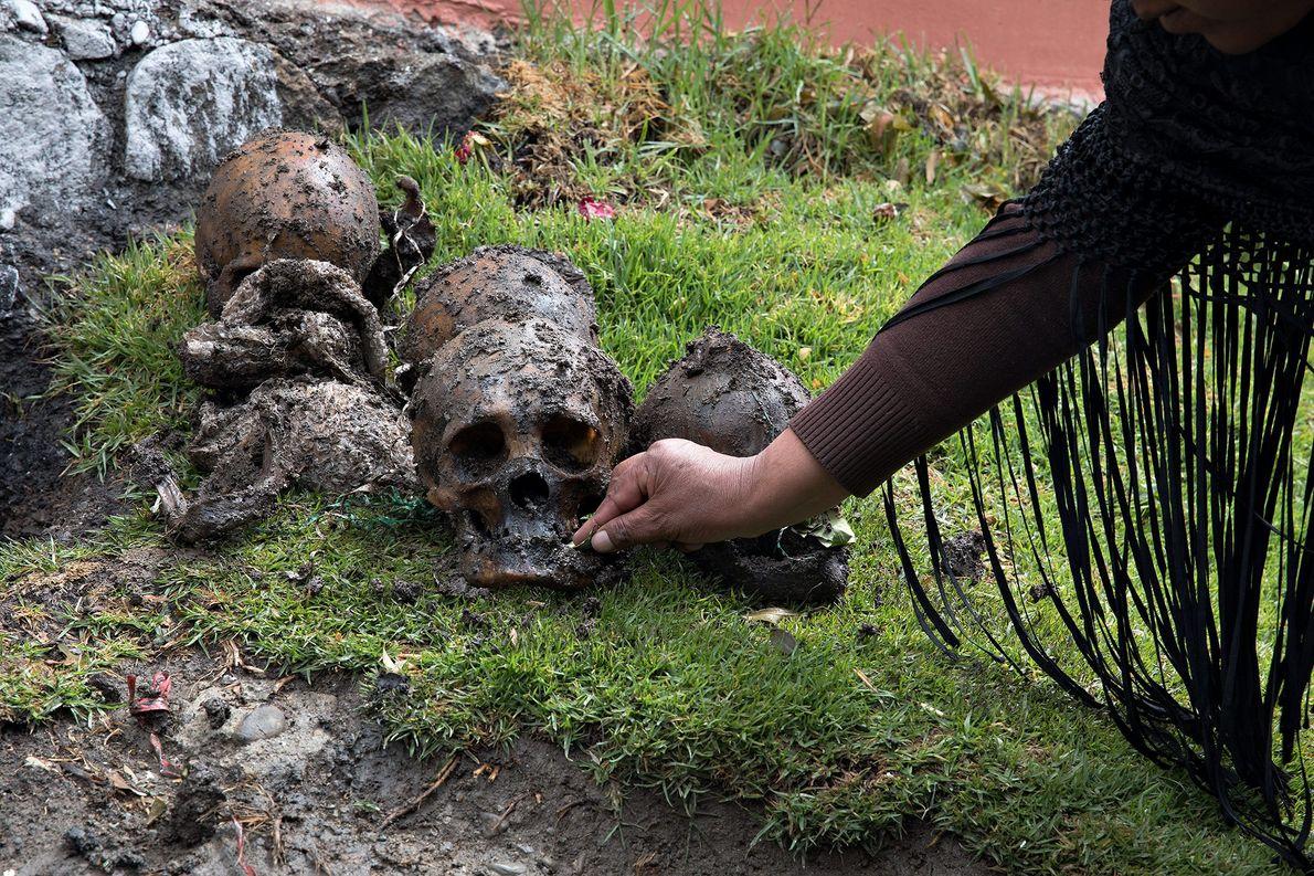 Un creyente ofrece una hoja de coca a la ñatita exhumada. La coca es una parte ...