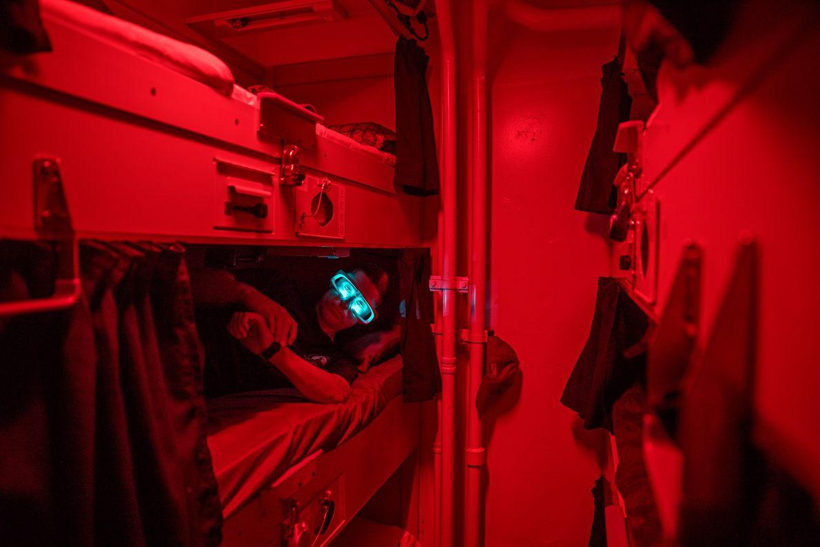Después de despertarse, el marinero Paul Hamilton descansa en su litera y usa gafas que emiten ...