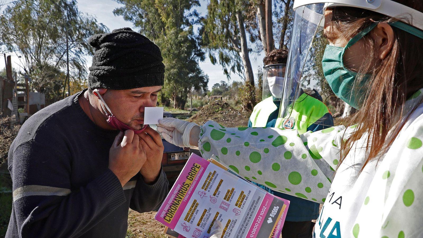 Una trabajadora sanitaria le hace un examen olfativo a un residente del barrio Altos de San ...