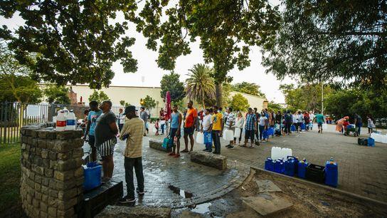 Los residentes hacen cola para llenar botellas de agua en un manantial de agua natural en ...