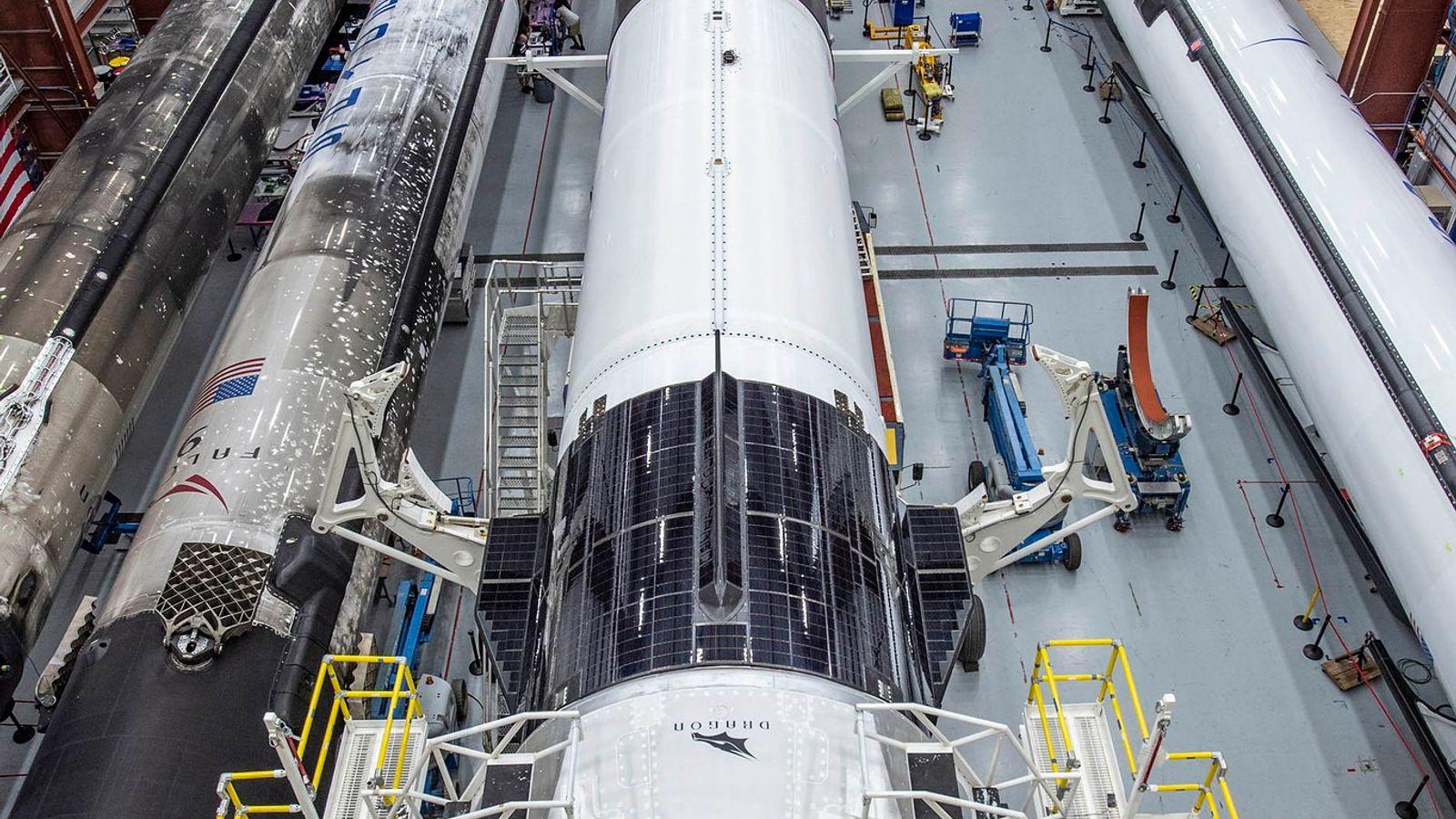 La nave espacial SpaceX Crew Dragon y el cohete Falcon 9 se sientan en el hangar ...