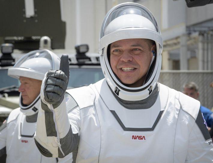 El astronauta Robert Behnken (primer plano) levanta el pulgar mientras se dirige a la plataforma de ...