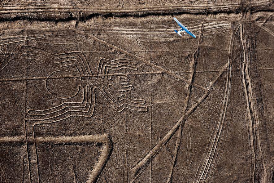 Un avión planea sobre un ancestral geoglifo de araña en el desierto de Perú.