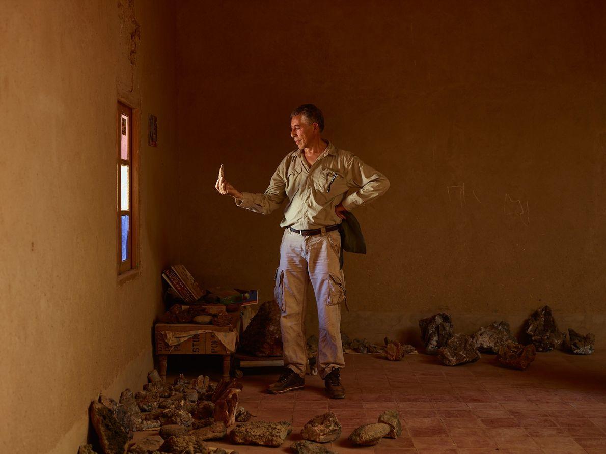 Samir Zouhri examina un gran diente del Spinosaurus en la casa de un aldeano en Taouz, ...