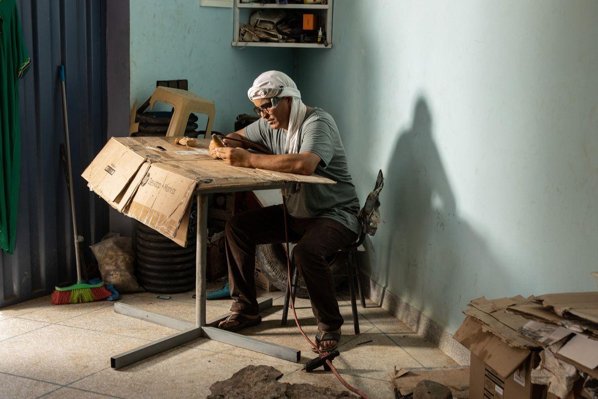Mohand Ihmadi, propietario del Centro de Trilobites Ihmadi en Alnif, Marruecos, prepara un diente del Spinosaurus ...