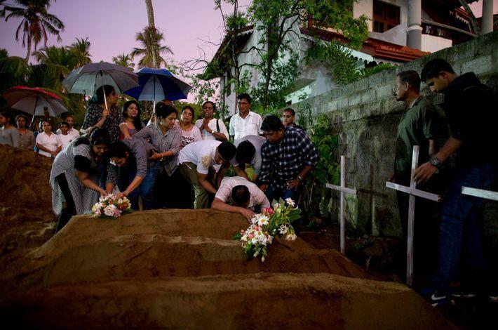 Los familiares colocan flores durante el entierro de tres víctimas en la misma familia, quienes murieron ...