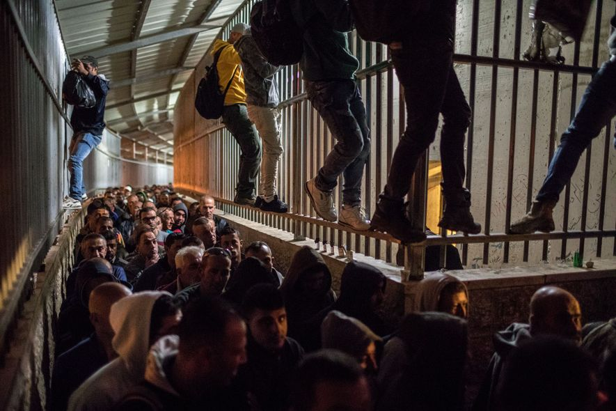 At Checkpoint 300 near Bethlehem, Palestinians from the West Bank, some climbing the walls to cut ...