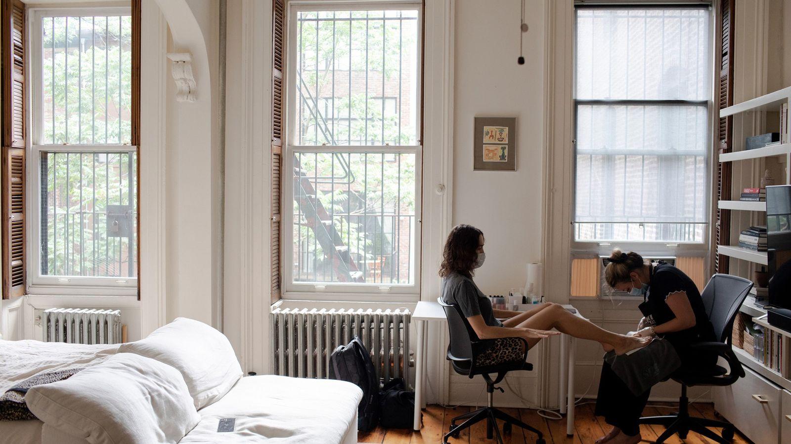 En Nueva York, una mujer utiliza el servicio de manicura y pedicura a domicilio durante la ...
