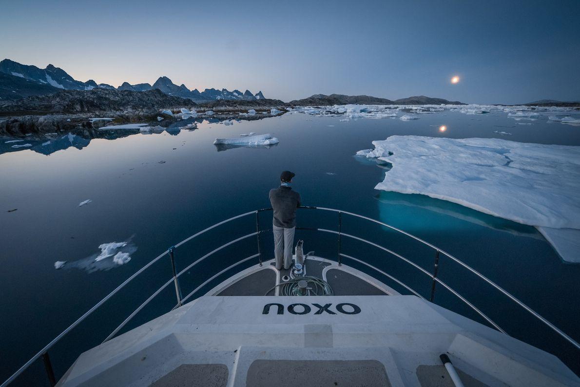 Un hombre atento mientras su bote va cruzando los icebergs en el mar de Groenlandia al ...