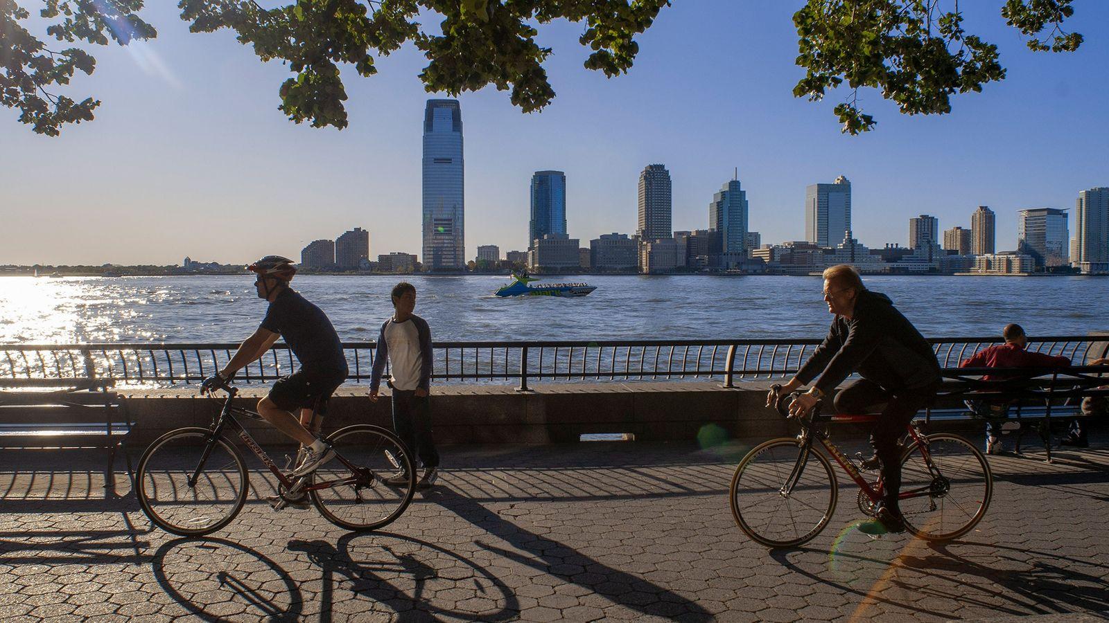 Los ciclistas dan un vistazo por el puerto de Nueva York y el horizonte de Nueva ...