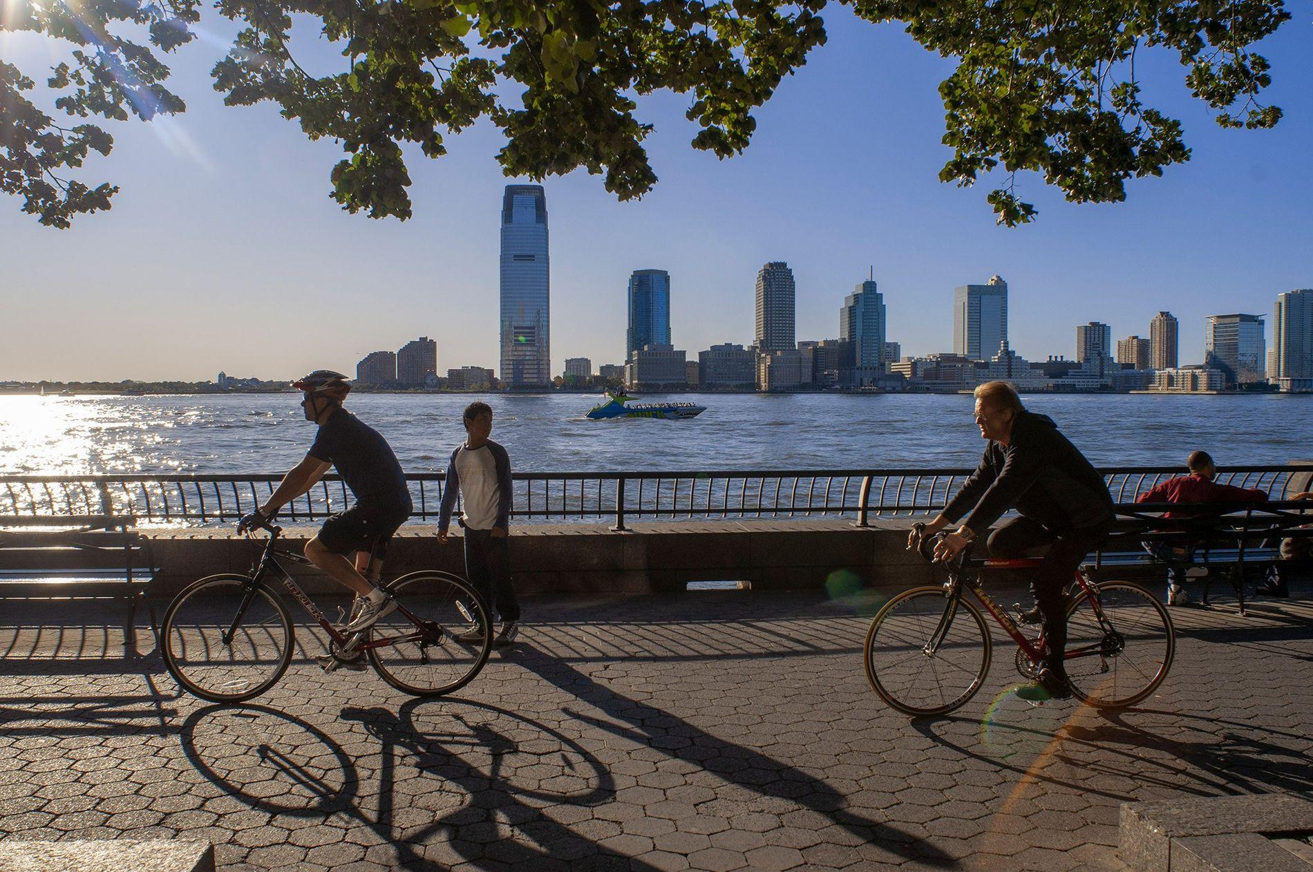 Los ciclistas dan un vistazo por el puerto de Nueva York y el horizonte de Nueva Jersey mientras pedalean por Battery Park.