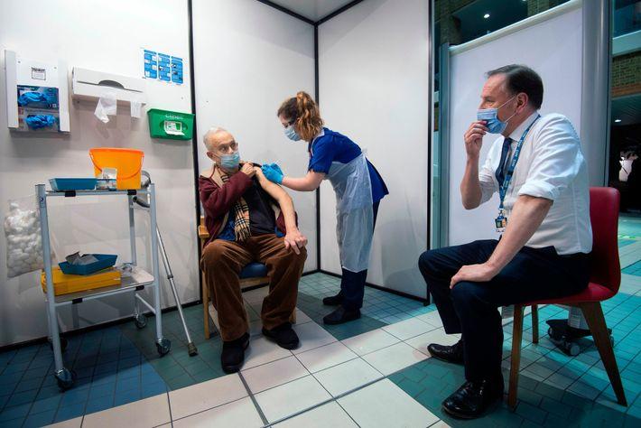 Simon Stevens (derecha), director ejecutivo del Servicio Nacional de Salud del Reino Unido, observa cómo una ...
