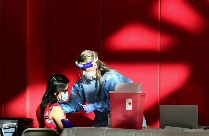 Una enfermera administra la vacuna anti-COVID-19 a una mujer en el gimnasio del Instituto Corona en ...