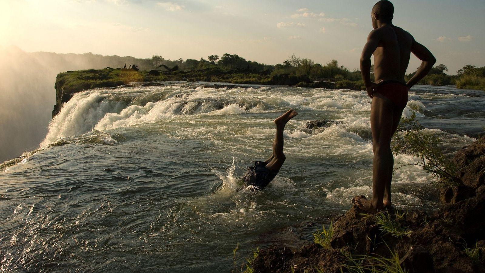 Dos hombres se zambullen en un estanque sobre las cataratas Victoria.