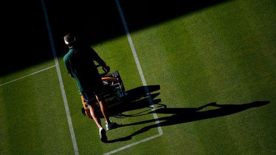 Un encargado corta el césped de la Cancha Central del Club de Tenis All England el ...