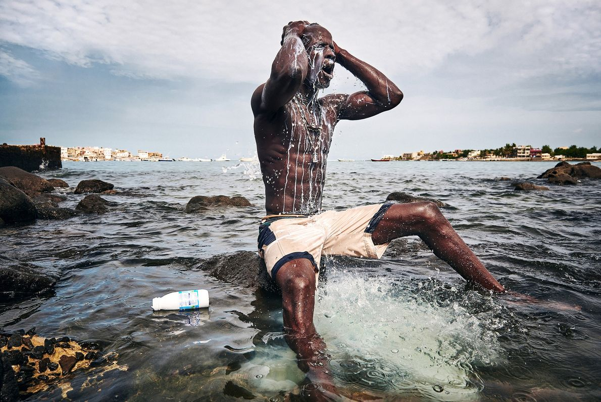 Kherou Ngor, un joven campeón de lucha, se lava con leche en la costa de Ngor, ...