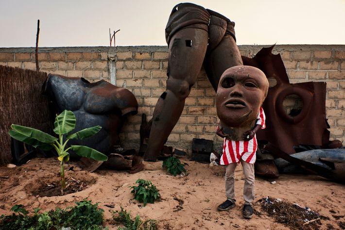 Una estatua de la leyenda de la lucha libre senegaesa Yekini está desmontada en un jardín ...