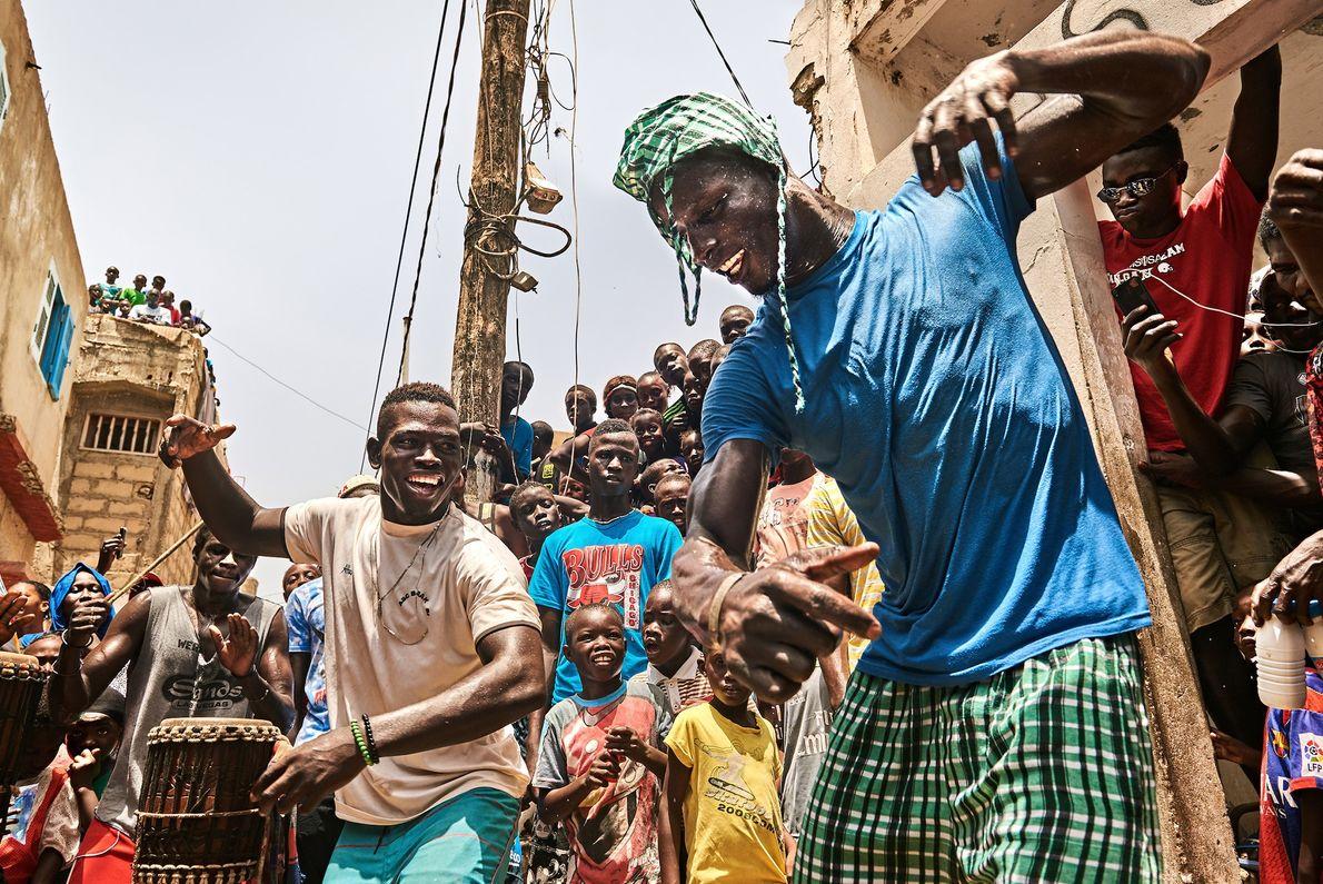 La gente se reúne frente a la casa de Kherou Ngor para ver al joven luchador ...