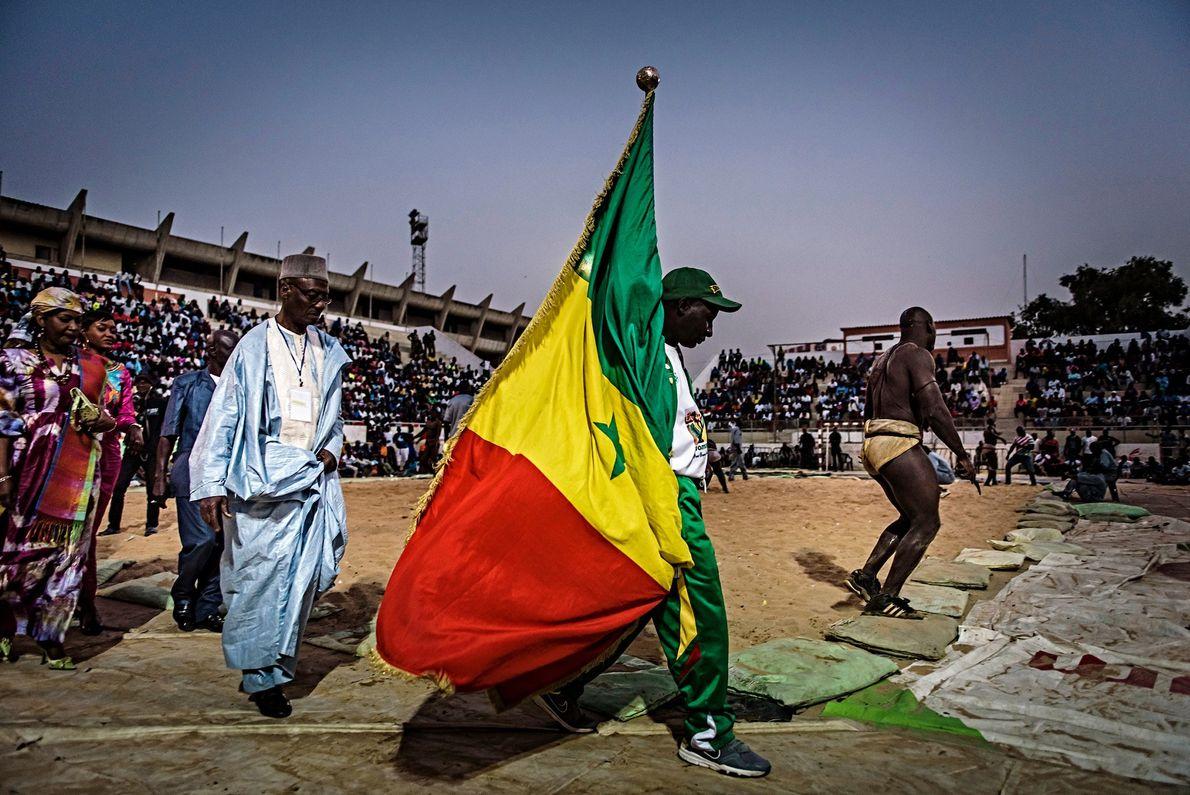 Los abanderados llevan la bandera senegalesa a través del estadio Iba Mar Diop en Dakar antes ...