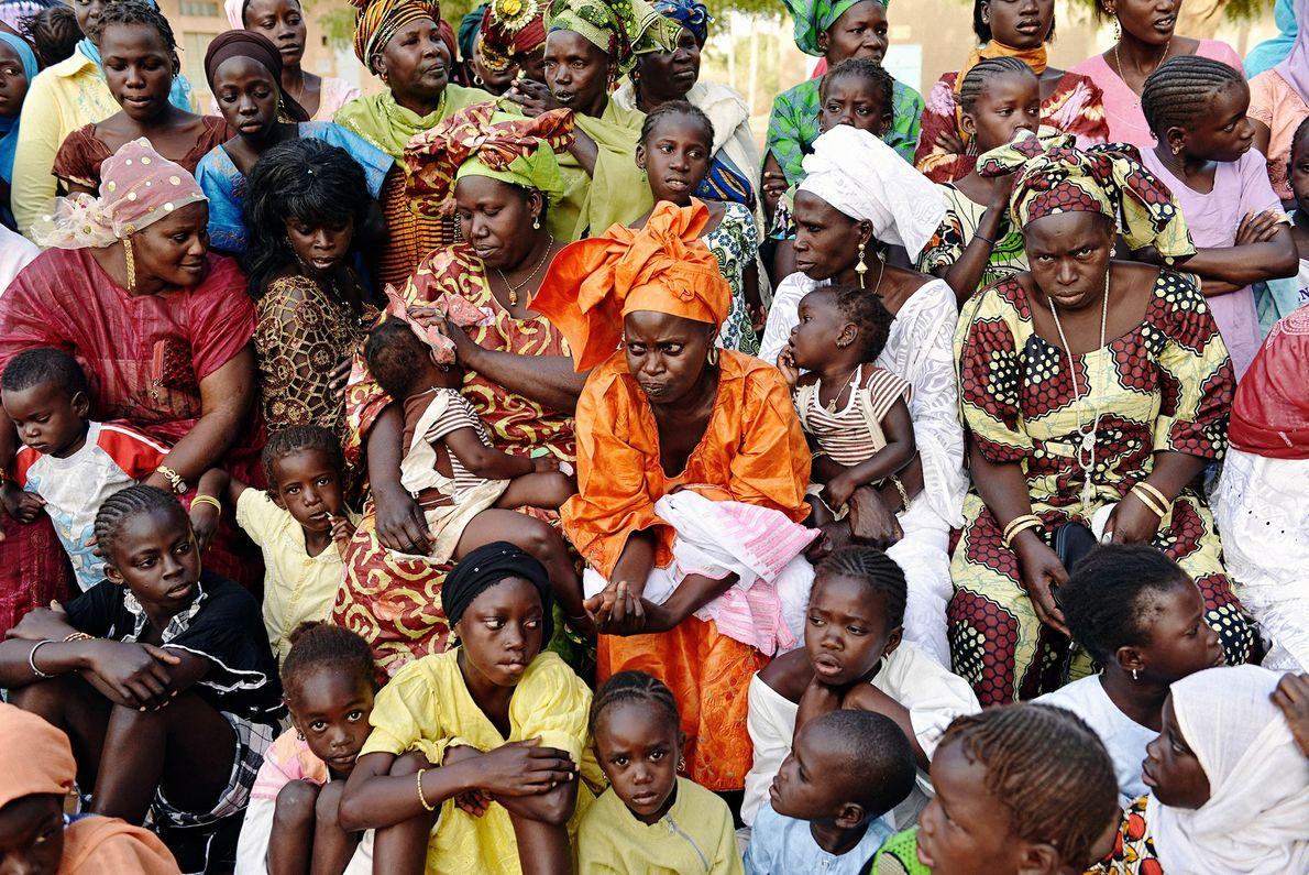 Mujeres y niños de la aldea senegalesa de Soune se reúnen para ver un combate de ...