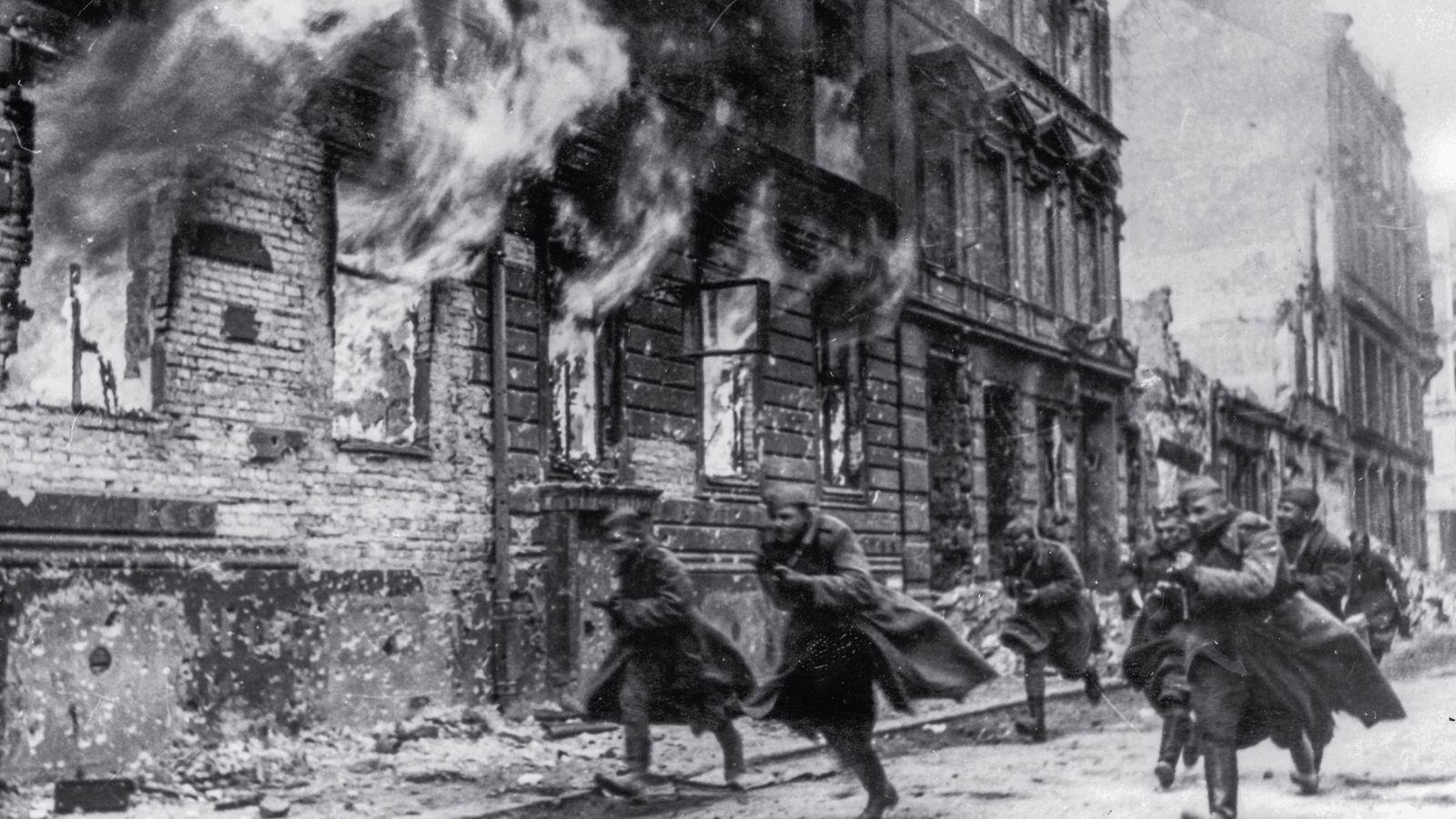 Apresurándose para reclamar Berlín, su premio, los soldados soviéticos corren por las calles de la condenada ...
