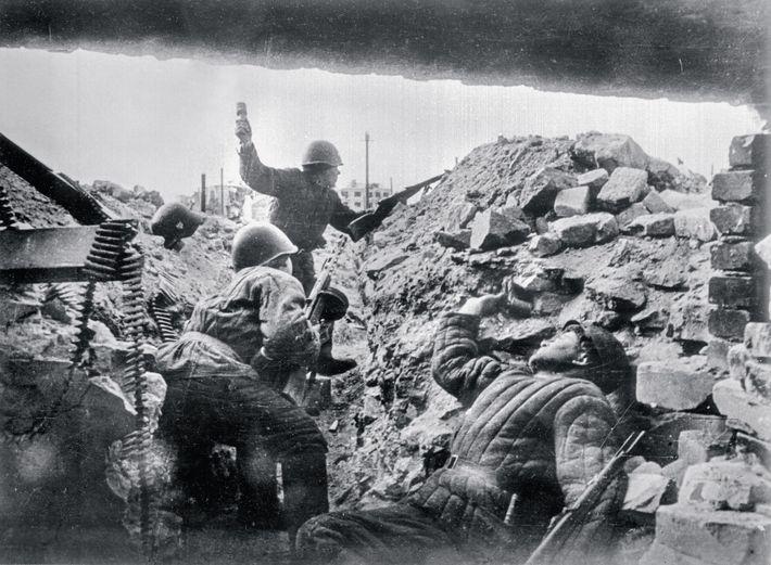 Un soldado soviético caído sostiene una granada de mano mientras otro les apunta a los invasores ...