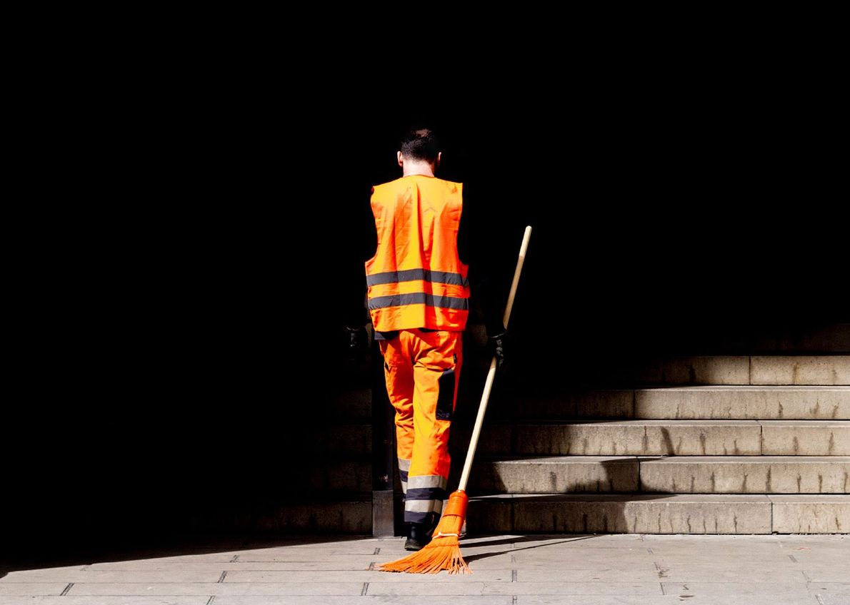 Múnich, Alemania El vibrante naranja del uniforme del trabajador de saneamiento de la ciudad y la escoba ...